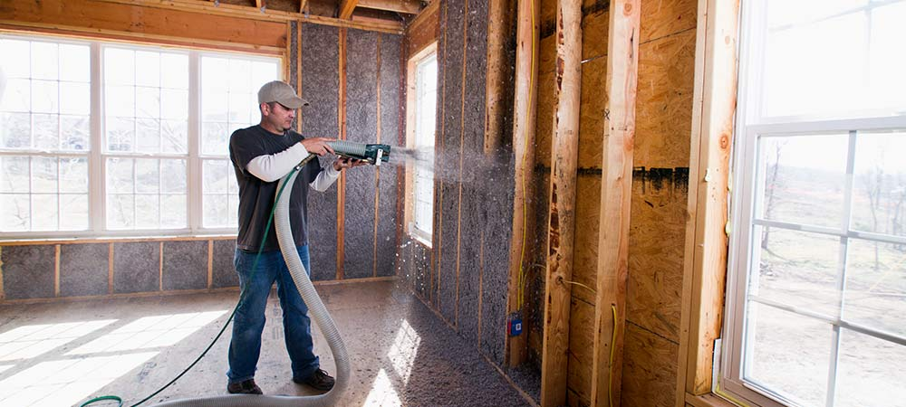 Professional Insulation Contractor Scraping Wall Sprayed with Fiberlite Cellulose Insulation6050